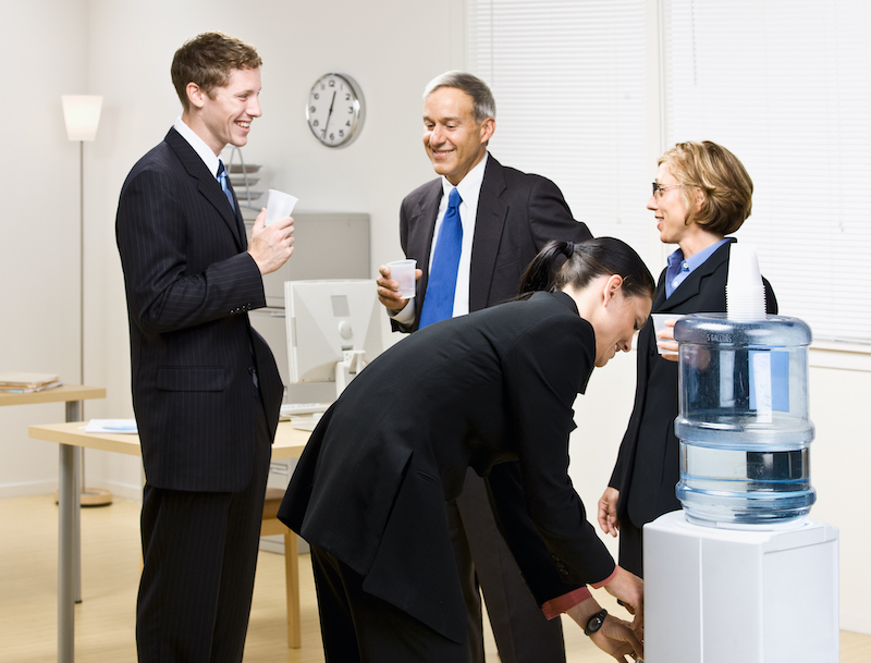 A photo of a group of people gathered around an office water cooler having a conversation